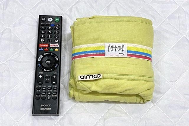 エアリコの抱っこ紐とテレビのリモコンのサイズを比較した画像
